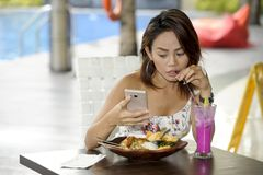 Young happy Asian woman in sexy dress outdoors having brunch or. Young beautiful and happy Asian woman in sexy dress sitting at pool holiday resort having brunch Royalty Free Stock Images