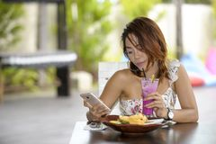 Young happy Asian woman in sexy dress outdoors having brunch or. Young beautiful and happy Asian woman in sexy dress sitting at pool holiday resort having brunch Royalty Free Stock Image