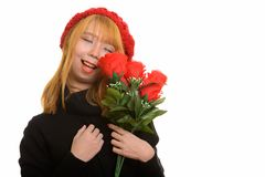 Young happy Asian woman smiling with eyes closed holding red ros. Es royalty free stock photography