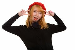 Young happy Asian woman smiling and making peace sign with both. Hands stock images