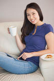 Young happy asian woman using her tablet pc and holding mug of c Royalty Free Stock Images