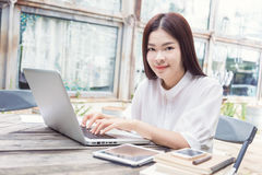 Young happy asian woman using technology on her laptop computer Stock Images