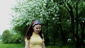 Young happy asian woman walking in spring park with shopping bags in hands. stock video footage