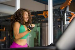 Young happy and athletic Asian Indonesian sport woman running on treadmill at gym fitness club training hard jogging workout. Focused and concentrated in stock photo