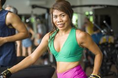 Young happy and athletic Asian Indonesian sport woman running on treadmill at gym fitness club training hard jogging workout. Focused and concentrated in royalty free stock images