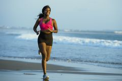 Young happy and attractive African American runner woman exercising on running workout at beautiful beach jogging and enjoying sun royalty free stock images