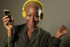 Young happy and attractive afro American woman with yellow headphones and mobile phone listening to internet music song smiling ch stock image