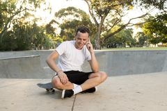 Young happy and attractive American man 30s sitting on skate board after sport boarding training session talking on mobile phone stock photo