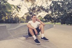 Young happy and attractive American man 30s sitting on skate board after sport boarding training session talking on mobile phone royalty free stock photo