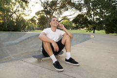 Young happy and attractive American man 30s sitting on skate board after sport boarding training session talking on mobile phone royalty free stock image