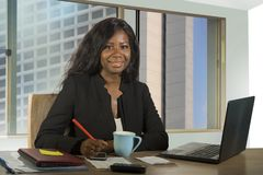 Young happy and attractive black African American businesswoman working confident at computer desk smiling satisfied in financial. Office corporate portrait of stock photos