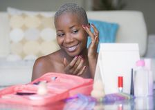 Young happy and attractive black african American woman wrapped in towel applying makeup cosmetics using fingers putting base prim stock photography