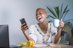 Young happy and attractive black afro american hipster woman working at home office with laptop computer using internet on mobile. Phone smiling in digital stock photography