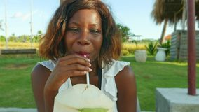 Young happy and attractive black afro American woman lying drinking coconut water at tropical resort garden stock footage