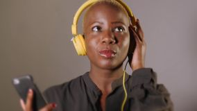 Young happy and attractive Afro American woman with yellow headphones and mobile phone listening to internet music song smiling stock video