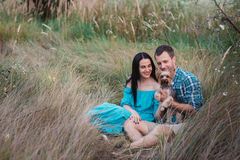 Young happy attractive couple posing with their dog - yorkshire terrier on nature. Love,lifestyle,relationship Royalty Free Stock Image
