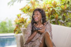 Young happy and attractive elegant black African American woman watching television holding controller having fun laughing on stock photography