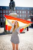 Young happy attractive exchange student girl having fun in town visiting Madrid city showing Spain flag. Having fun outdoors in tourism and travel vacation royalty free stock images