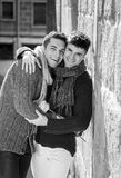 Young happy attractive gay men couple holding rose hugging and kissing outdoors Valentines free homosexual love Stock Image
