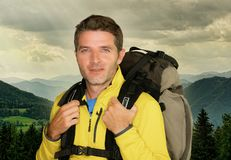 Young happy and attractive hiker man carrying backpack posing cheerful during mountain hike smiling enjoying beautiful nature trip stock image