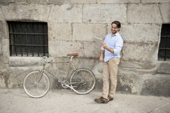 Man smiling using internet with digital tablet pad on vintage cool retro bike Royalty Free Stock Photos