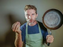 Young happy and attractive home cook man holding cooking pan smiling satisfied and proud giving delicious hand fingers sign as dom. Young happy and attractive Royalty Free Stock Images