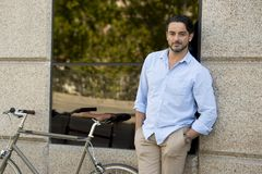 Happy attractive latin man in casual trendy clothes smiling cheerful riding on vintage cool retro bicycle Royalty Free Stock Photo