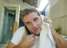 Young happy and attractive man drying with towel after washing face at home bathroom mirror while speaking on the mobile phone smi. Ling cheerful and natural in stock photos