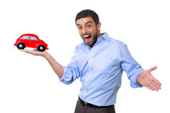 Young happy attractive man pointing big red toy car on his hand Royalty Free Stock Photo