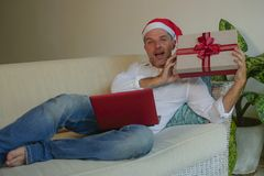 Happy and attractive man in Santa hat using credit card and laptop computer buying online Christmas presents holding gift box stock photography