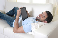 Young happy attractive man using digital pad or tablet sitting on couch Stock Photo