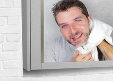 Young happy attractive man using towel drying face after washing looking at the bathroom mirror smiling cheerful and positive feel. Young happy and attractive stock photography