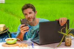Young happy and attractive man working outdoors with laptop computer and mobile phone as internet travel blogger or digital nomad. Backpacker sitting relaxed at Stock Photo
