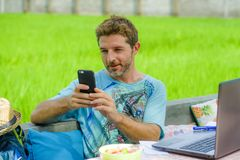Young happy and attractive man working outdoors with laptop computer and mobile phone as internet travel blogger or digital nomad. Backpacker sitting relaxed at Royalty Free Stock Photo