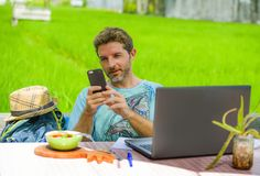 Young happy and attractive man working outdoors with laptop computer and mobile phone as internet travel blogger or digital nomad. Backpacker sitting relaxed at Stock Photos