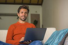 Young happy and attractive man working relaxed with laptop computer at modern apartment living room sitting at sofa couch typing a. Nd networking in entrepreneur royalty free stock images