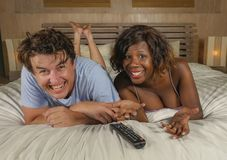 Young happy and attractive mixed ethnicity couple with beautiful black afro American woman and cheerful white man at home lying on. Bed watching tv show or royalty free stock images