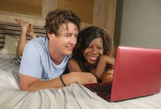 Young happy and attractive multiracial couple with beautiful black African American ethnicity woman and white man lying relaxed on. Bed shopping online using stock photo