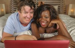 Young happy and attractive multiracial couple with beautiful black afro American ethnicity woman and white man lying relaxed on. Young happy and attractive royalty free stock photography