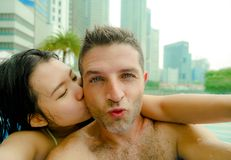 Young happy and attractive playful couple taking selfie picture together with mobile phone at luxury urban hotel infinity pool enj. Oying holidays honeymoon stock images