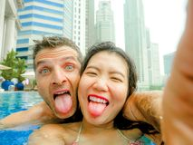 Young happy and attractive playful couple taking selfie picture together with mobile phone at luxury urban hotel infinity pool enj. Oying holidays honeymoon royalty free stock photo