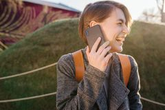 Young happy attractive short-haired brunette woman with phone in a park royalty free stock image