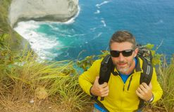Young happy and attractive sporty hiker man with trekking backpack hiking at sea cliff landscape feeling free enjoying travel royalty free stock image