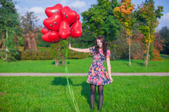 Young happy attractive woman in beautiful dress with red balloons walking outside Royalty Free Stock Images