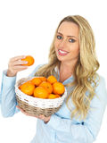 Young Happy Attractive Woman Holding a Basket of Tangerines Stock Images