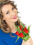 Young Happy Attractive Woman Holding a Bunch of Red Tulips Royalty Free Stock Photography
