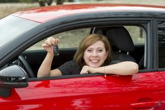 Attractive woman smiling proud sitting at driver seat holding and showing car key in new automobile buying and renting Royalty Free Stock Photography