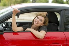Attractive woman smiling proud sitting at driver seat holding and showing car key in new automobile buying and renting Royalty Free Stock Image