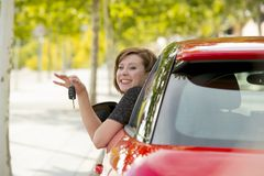 Attractive woman smiling proud sitting at driver seat holding and showing car key in new automobile buying and renting Stock Photography