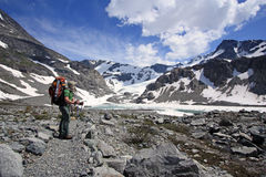 Young happy backpacker enjoying the mountain views. Royalty Free Stock Images